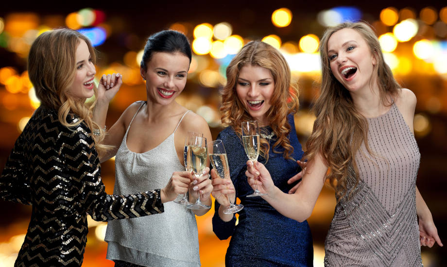 Happy women clinking champagne glasses over lights